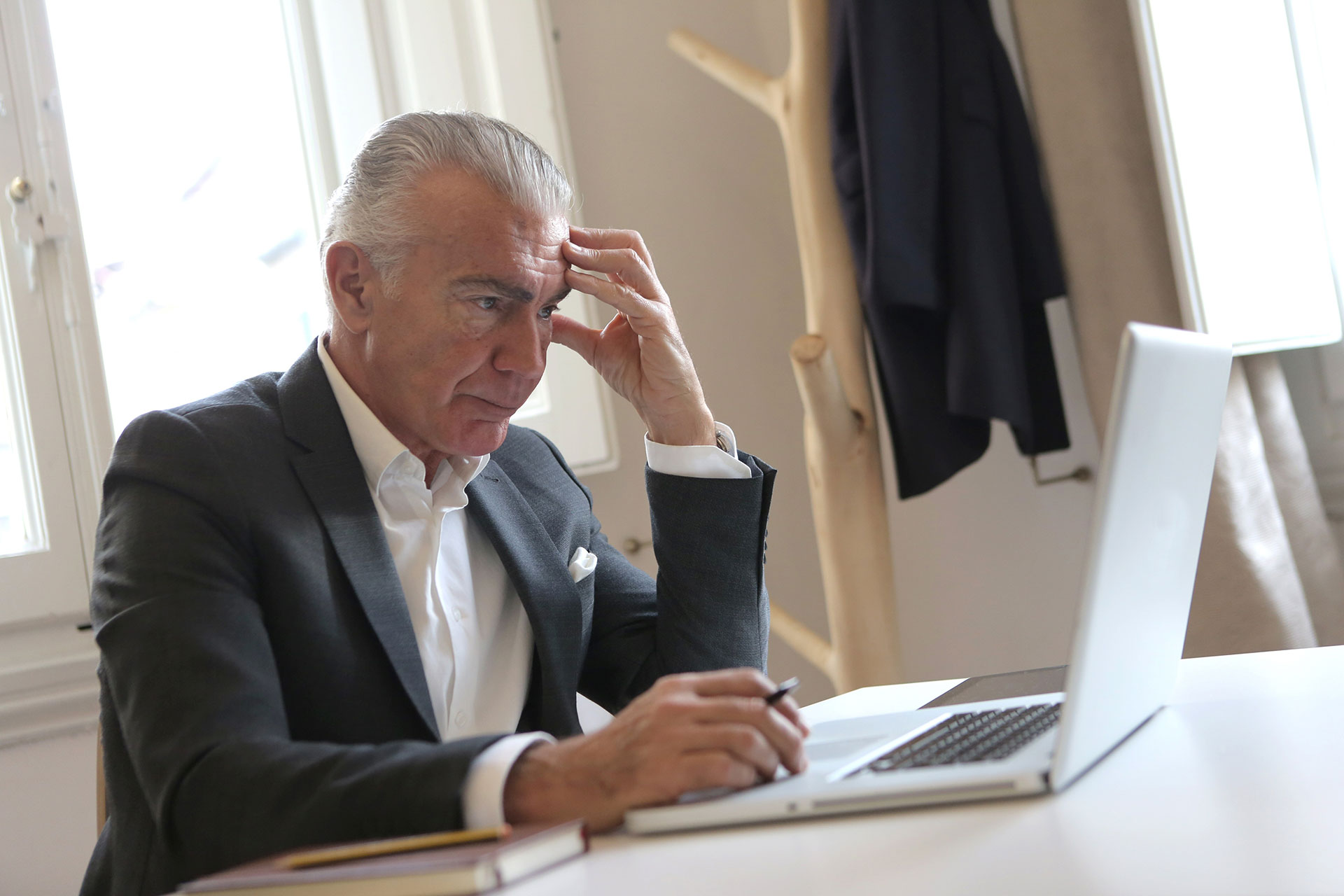 Man slightly stressed in Black Suit Jacket While Using Laptop