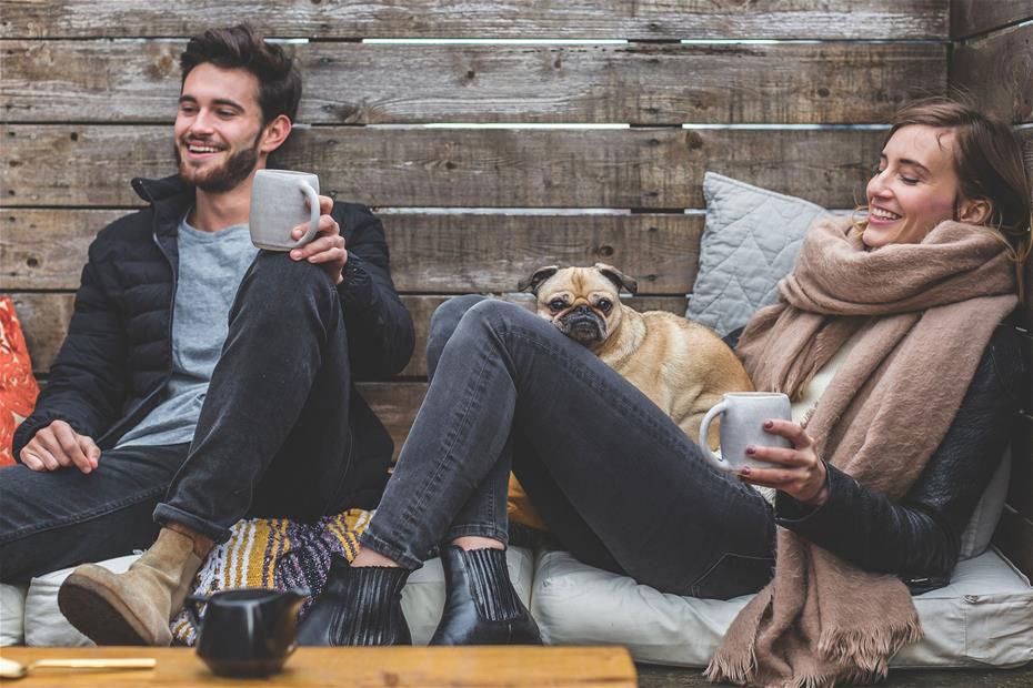 Man and woman happily enjoying home with their dog