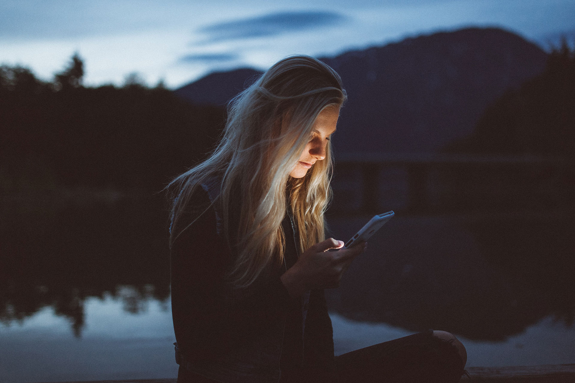 Female on phone by a lake at night