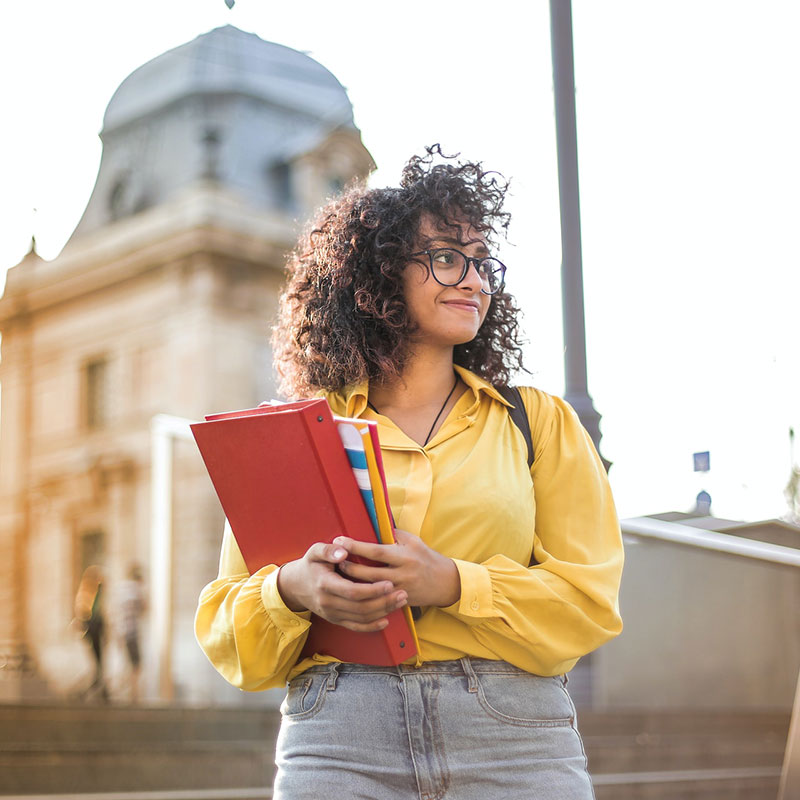 Female Student In Yellow Jacket Holding Books