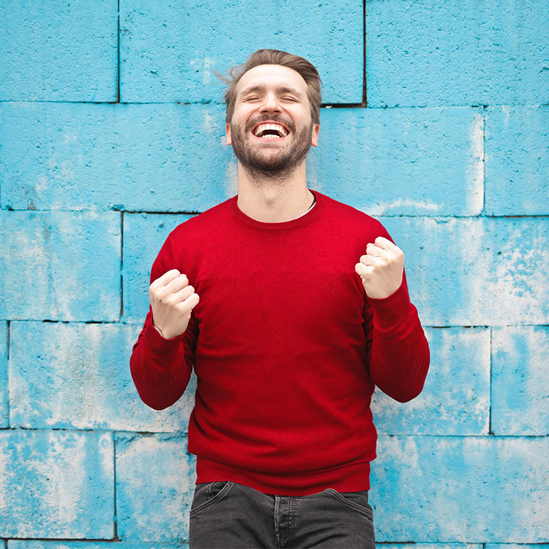 Man Rejoicing In Front of blue wall