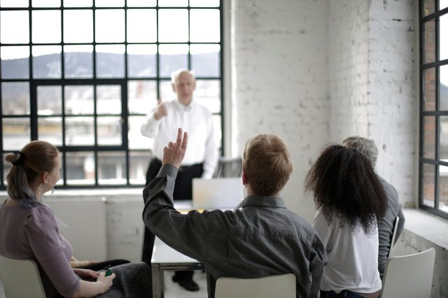 People having a meeting with one person raising their hand