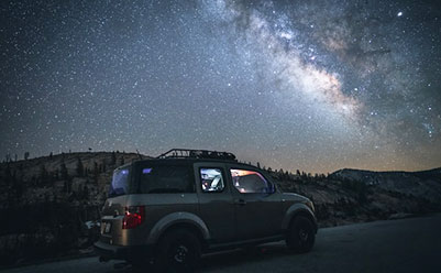 Car driving at night under the stars