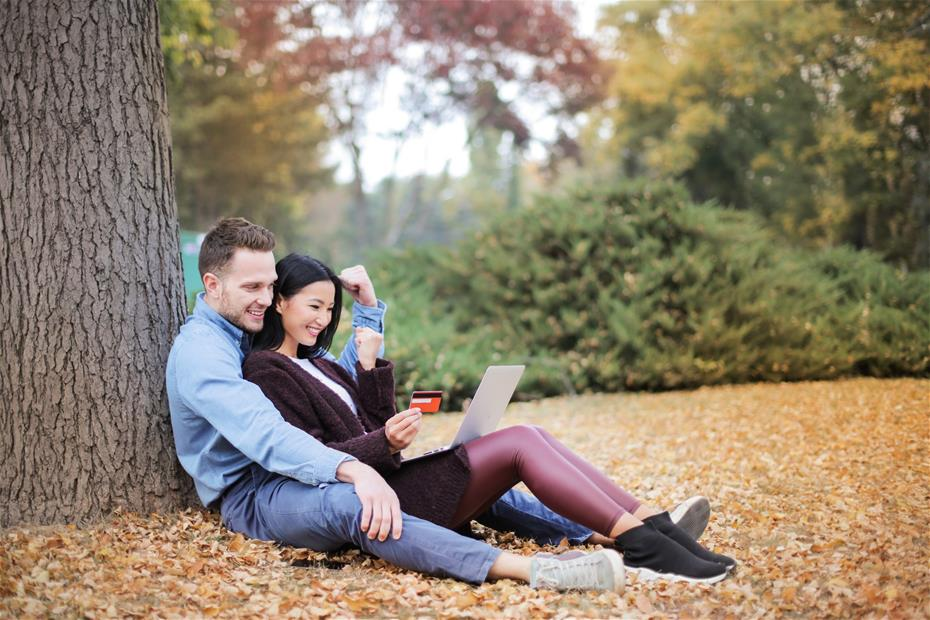 Couple Reclining Beside Tree Trunks using a credit card to buy something online