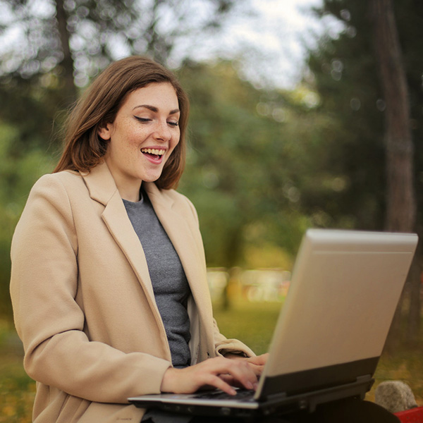 Excited Woman Using Computer Laptop outside