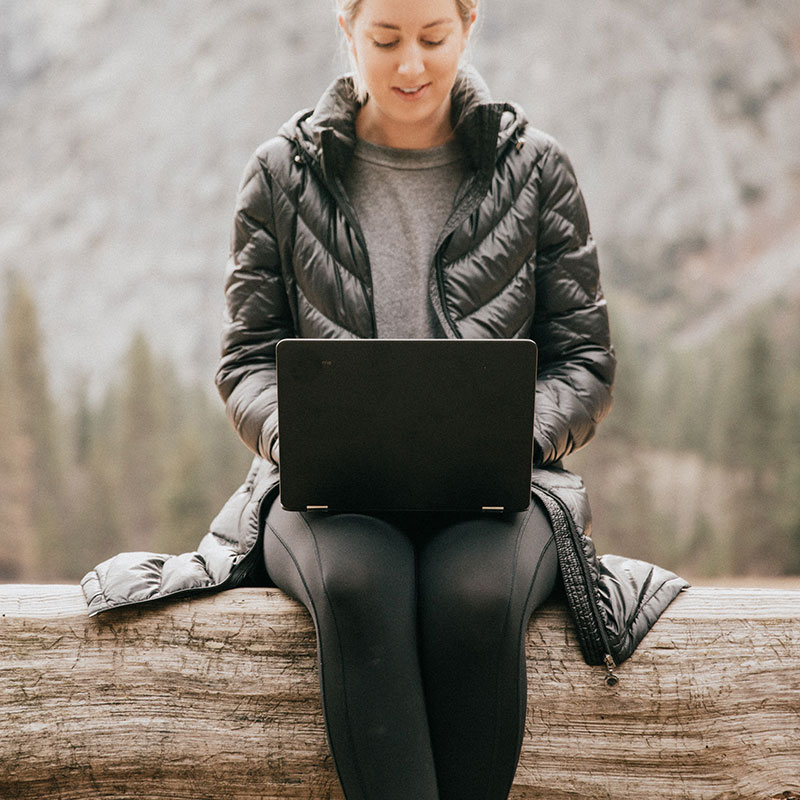 Female on computer in the wilderness