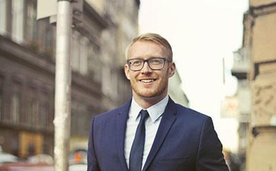 Happy man in black suit walking through a city