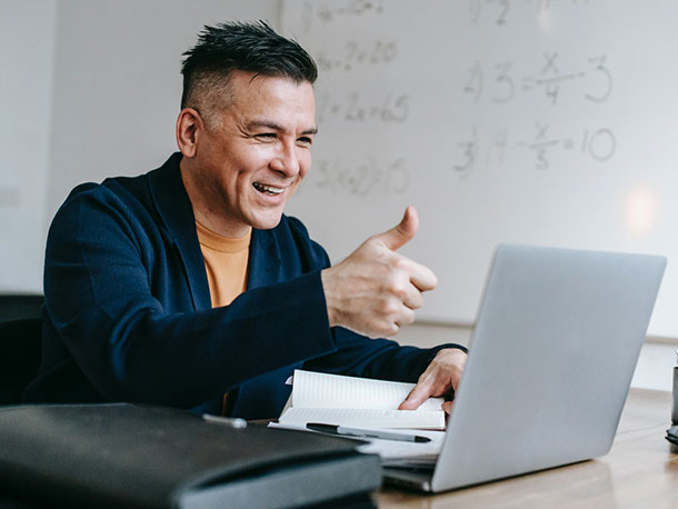 Man on laptop giving Thumbs Up