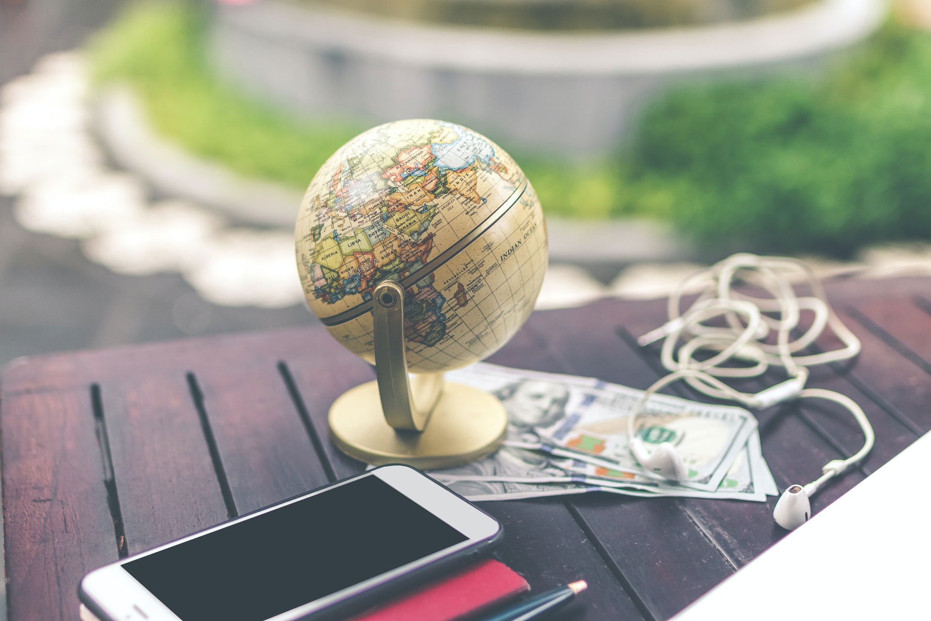 Mini globe outside on table with money