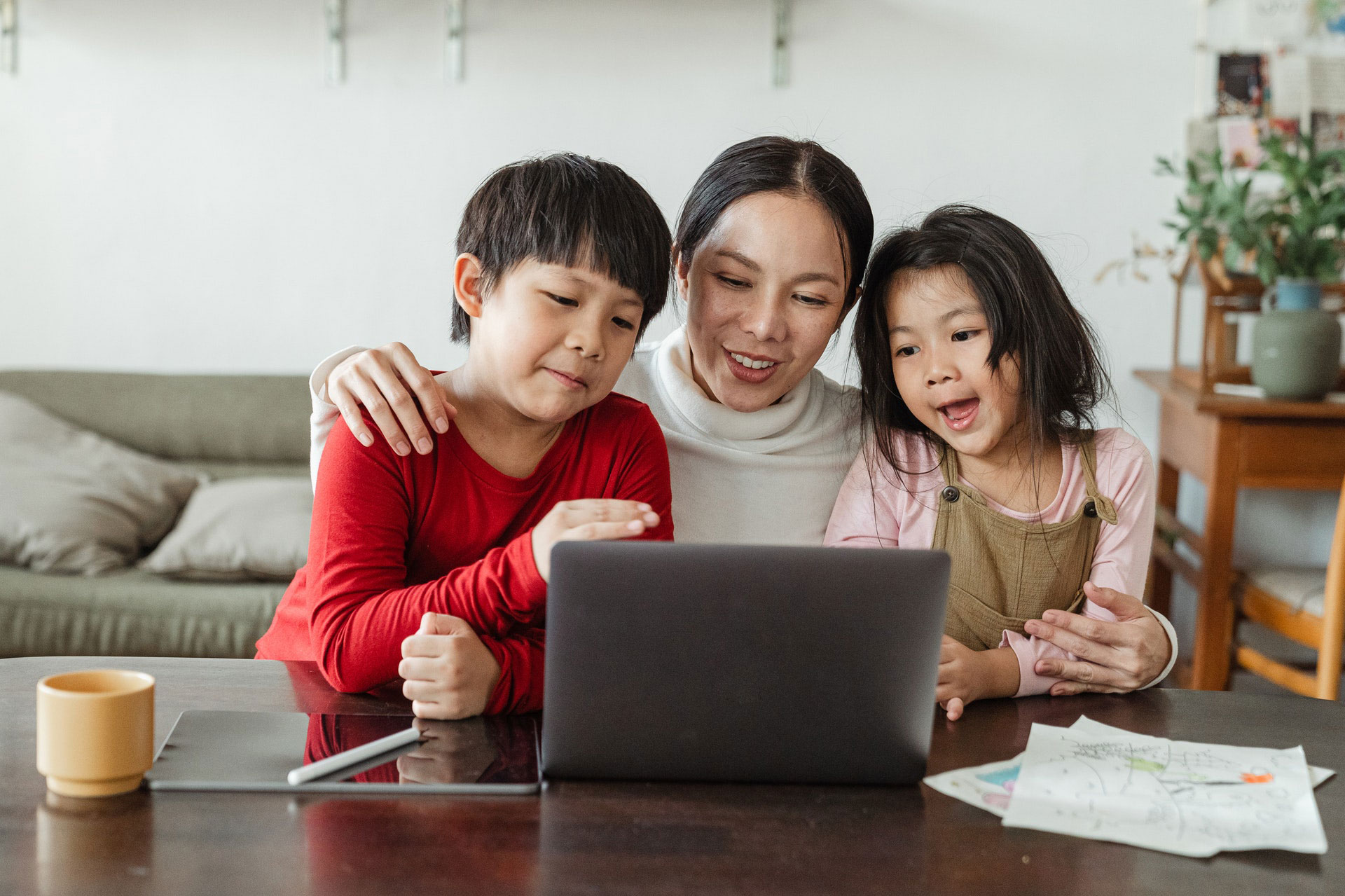 Mother with her son and daughter happily on computer at home