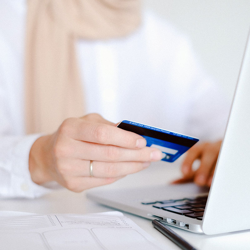 Person in White Long Sleeve Shirt Holding Credit Card on computer