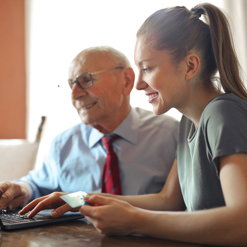 Senior and young adult happily working together on a computer in an office