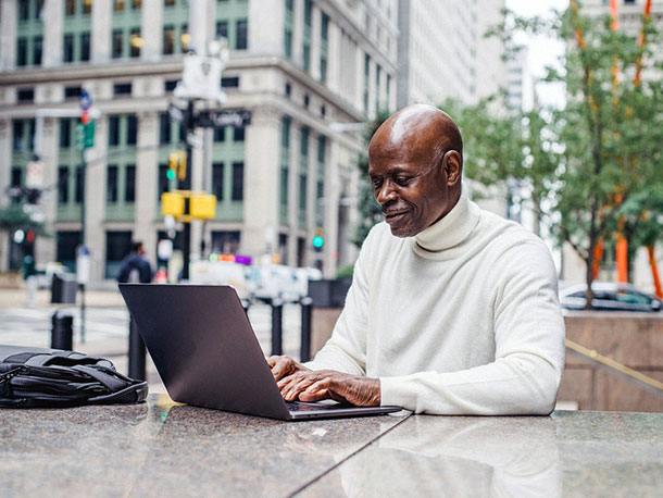 Smiling black business man with laptop on street