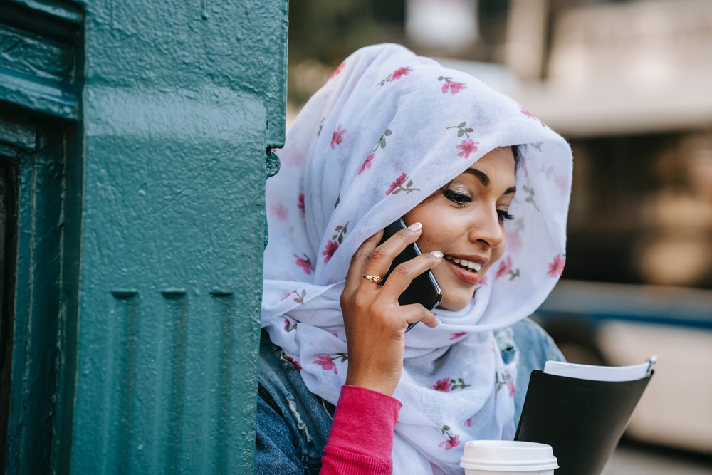 Smiling ethnic woman talking via modern smartphone in city street