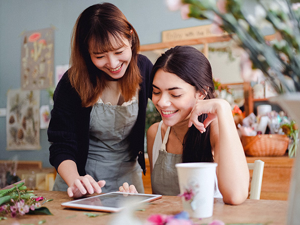 Smiling female florists browsing tablet at work