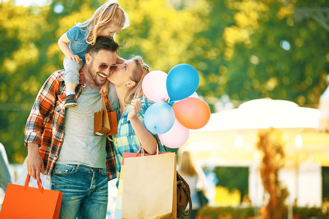 Earn points from your everyday purchases! Family at a carnival.