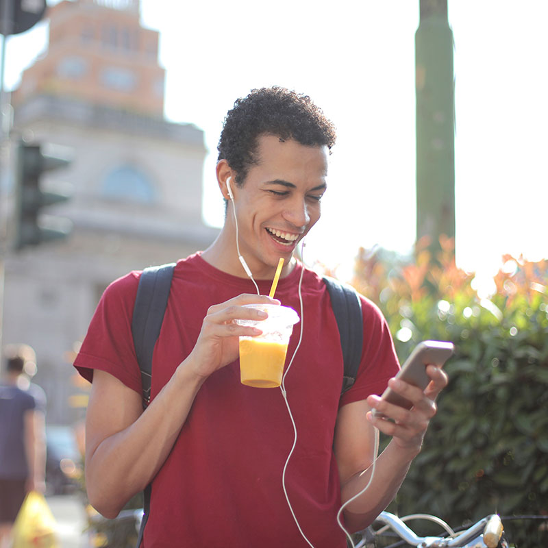 Male outside drinking a smoothie on his phone smiling
