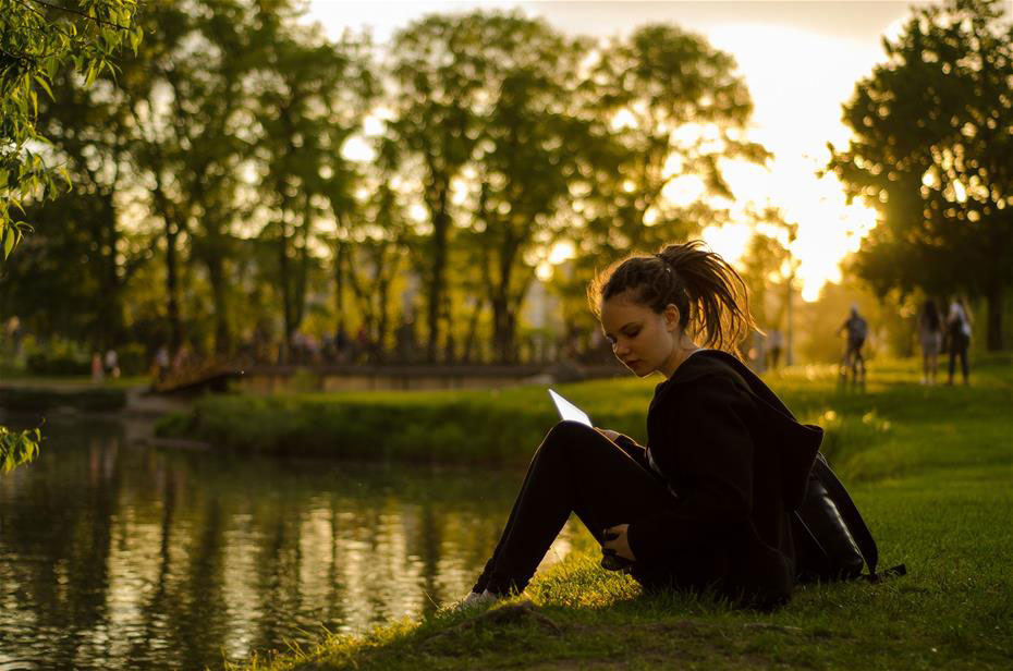 Female College Student sitting by a lake